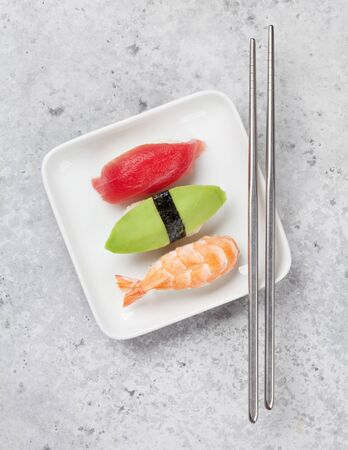 Japanese sushi set. Sashimi, maki rolls. On plate over stone background. Top view flat lay Stock Photo - 128198602