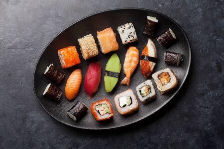 Japanese sushi set. Sashimi, maki rolls. On plate over stone background. Top view flat lay Stock Photo - 128198900