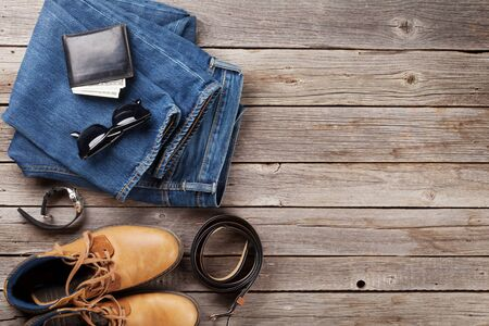 Men's clothes and accessories. Jeans, shoes, glasses and wallet with cash on wooden background. Top view with copy space
