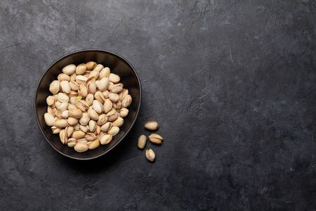 Beer snacks. Pistachio nuts bowl. Top view with copy space. Flat lay Archivio Fotografico - 128398934