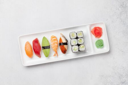 Japanese sushi set. Sashimi, maki rolls. On plate over stone background. Top view flat lay with copy space for your text Stock Photo - 128758331