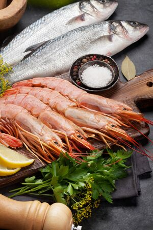 Fresh seafood. Trout fish and langostino shrimps with herbs and spices on a stone background Archivio Fotografico - 128758625
