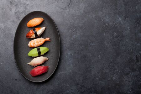 Japanese sushi set. Sashimi, maki rolls. On plate over stone background. Top view flat lay with copy space for your text Stock Photo - 128758783