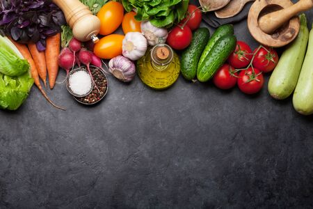 Assorted raw organic vegetables, herbs and spices. Fresh garden vegetarian food. Top view on stone table with copy space Imagens