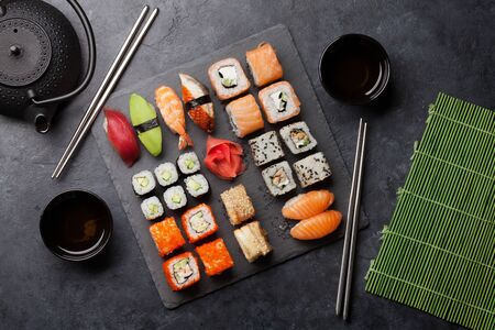 Japanese sushi set. Sashimi, maki rolls and green tea. On plate over stone background. Top view flat lay Stock Photo - 128758883