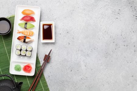 Japanese sushi set. Sashimi, maki rolls and green tea. On plate over stone background with space for your text. Top view flat lay Stock Photo