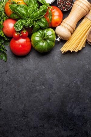 Pastas, tomates y hierbas. Cocinar los ingredientes en la mesa de piedra. Vista superior con espacio de copia. Endecha plana Foto de archivo