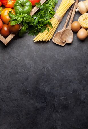 Pasta, tomatoes and herbs. Cooking ingredients on stone table. Top view with copy space. Flat lay