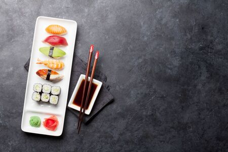 Japanese sushi set. Sashimi, maki rolls. On plate over stone background. Top view flat lay with copy space for text Stock Photo - 129007458