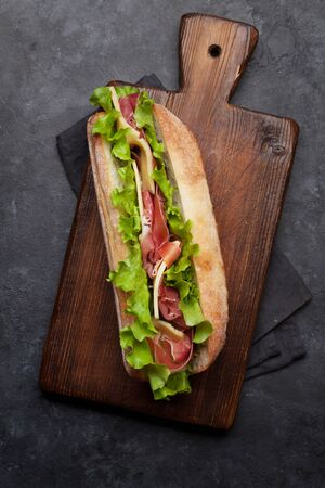Fresh submarine sandwich with prosciutto ham, cheese and lettuce on dark stone background. Top view Stock fotó