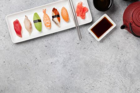 Japanese sushi set. Sashimi, maki rolls and green tea. On plate over stone background with space for text. Top view flat lay Stock Photo - 129007455