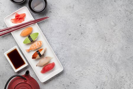 Japanese sushi set. Sashimi, maki rolls and green tea. On plate over stone background with space for text. Top view flat lay Stock Photo - 129007482