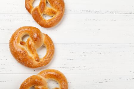Oktoberfest food backdrop. Pretzels on white wooden background. Top view with copy space. Flat lay Stock Photo