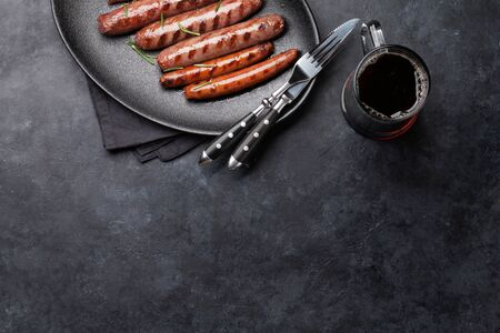 Grilled sausages with rosemary herbs and glass of dark beer. Top view with copy space