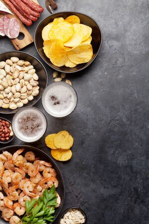 Draft beer and snacks on stone background. Nuts, chips, sausages and shrimps. Flat lay. Top view with copy space