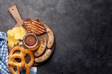 Oktoberfest set. Pretzels, sausages and chips on wooden board