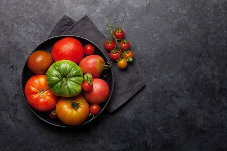 Fresh garden colorful tomatoes on stone kitchen table. 写真素材