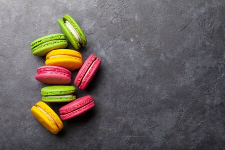 Cake macaron or macaroon sweets on stone backdrop. Top view flat lay with copy space