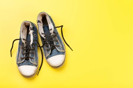 Old sneakers over yellow backdrop.