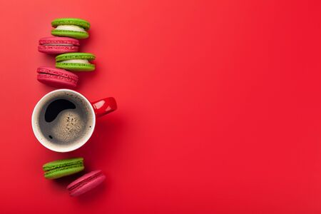 Cake macaron or macaroon sweets and coffee cup on red backdrop. Stock Photo