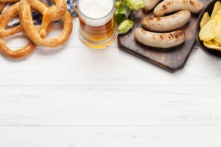 Oktoberfest set. Pretzels, sausages, meat and lager beer mug on wooden background. With copy space