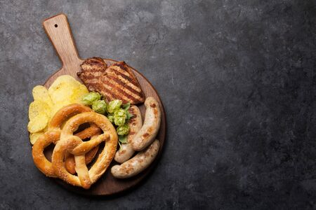 Oktoberfest set. Pretzels, sausages, meat and chips on stone background. With copy space. Top view flat lay