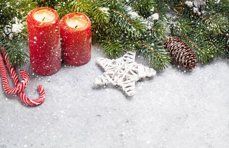 Christmas decor, candles and fir tree branch covered by snow on stone background 版權商用圖片 - 129953193