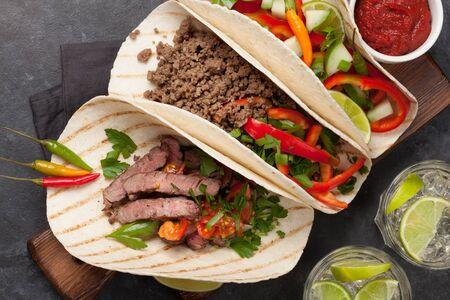 Conjunto de tacos mexicanos con carne y verduras. Y cóctel de caipirinha. Vista superior plana endecha