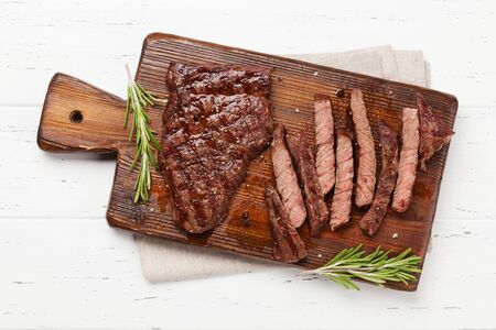 Grilled beef steak on wooden board. Top view flat lay