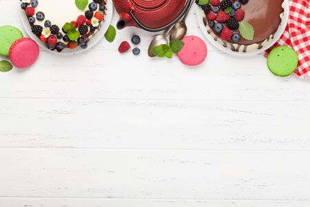 Chocolate cake and cheesecake with berries and tea. On wooden table with copy space. Top view flat lay Stock Photo