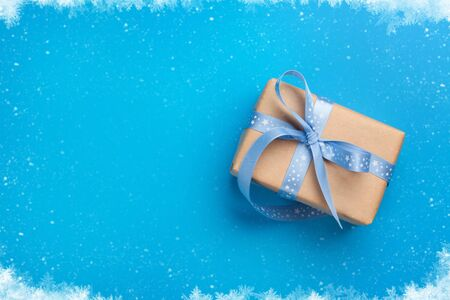 Christmas gift box on blue background. Top view with copy space