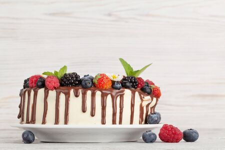 Chocolate cake or cheesecake with berries. On wooden table with copy space Stock Photo