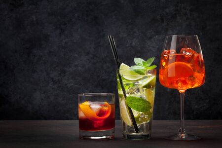 Three classic cocktail glasses on stone table. Negroni, aperitif and mojito. With copy space