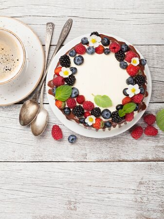 Chocolate cheesecake with berries and coffee cup. On wooden table with copy space. Top view flat lay