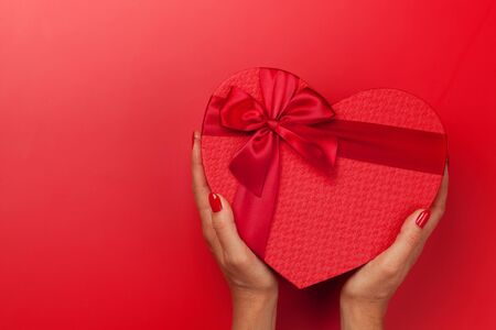 Woman hands holding Valentine's Day gift box on red background. Top view with copy space