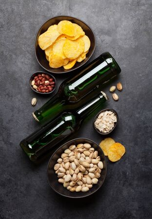 Bottled beer and snacks on stone background. Nuts and chips. Top view with copy space