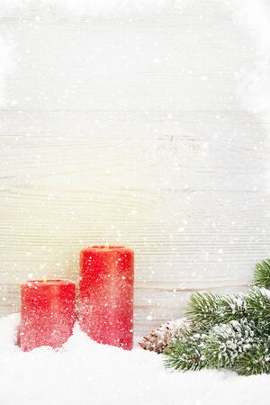 Christmas candles and fir tree branch covered by snow in front of wooden wall. View with copy space