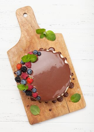 Chocolate cake or cheesecake with berries. On wooden table. Top view flat lay Stock Photo