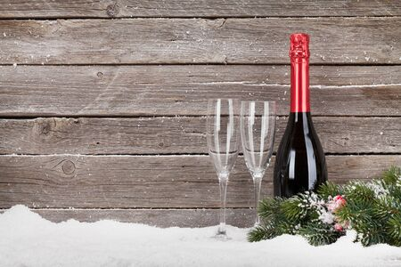 Christmas greeting card with champagne bottle in snow. View with space for greetings