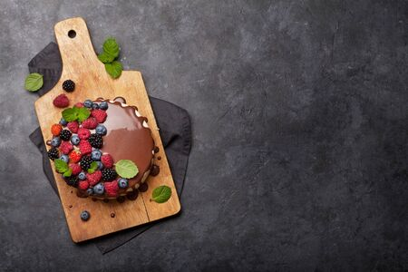 Chocolate cake or cheesecake with berries. On stone table with copy space. Top view flat lay Stock Photo