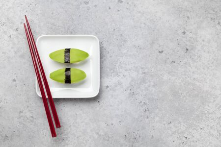 Japanese sushi set with avocado. On plate over stone background with space for text
