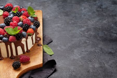 Chocolate cake or cheesecake with berries. On stone table with copy space