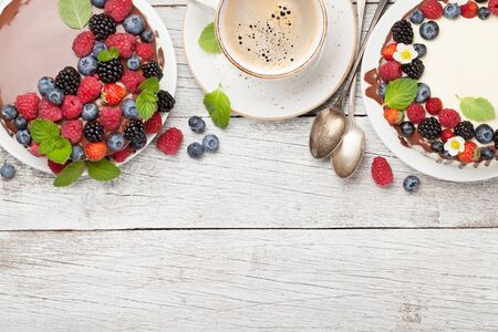 Chocolate cake and cheesecake with berries and coffee cup. On wooden table with copy space. Top view flat lay Stock Photo