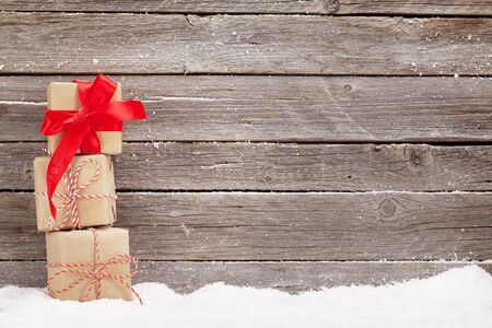 Christmas card with xmas gift boxes in front of wooden wall. With space for greetings