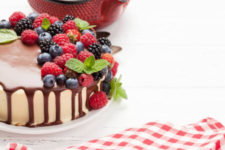 Chocolate cheesecake with berries and tea. On wooden table with copy space