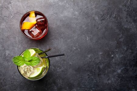 Two classic cocktail glasses on stone table. Negroni and mojito. Top view with copy space. Flat lay