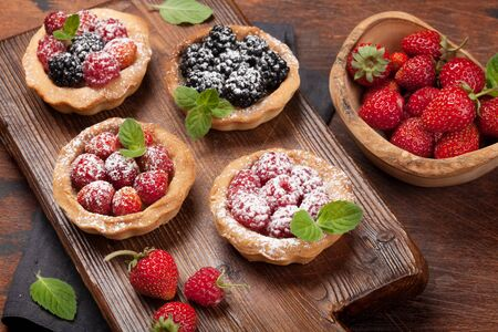 Set of sweet cakes with berries on wooden board. Strawberry, raspberry and blackberry