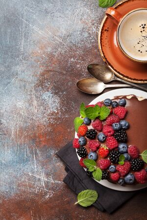 Chocolate cheesecake with berries and coffee cup. On stone table with copy space. Top view flat lay Stock Photo