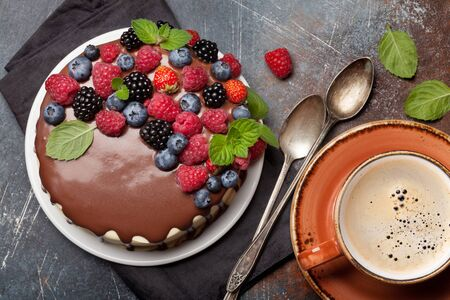 Chocolate cheesecake with berries and coffee cup. On stone table. Top view flat lay Stock Photo