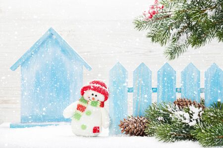 Christmas snowman toy, decor and fir tree branch. Xmas greeting card with space for greetings